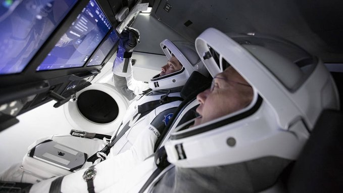 Inside SpaceX Dragon cabin showing two male astronauts looking at screens